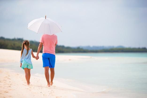 Hintere ansicht der familie am strand mit regenschirm