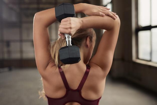 Hintere ansicht der fit muskulösen frau, die hantel-überkopf-trizepsverlängerungsübung während des funktionellen trainings im fitnessstudio tut