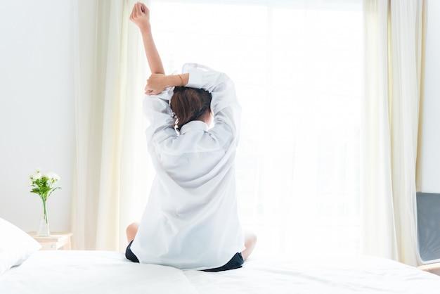 Hintere ansicht der frau ausdehnend in morgen, nachdem sie auf bett nahe fenster aufwacht worden ist