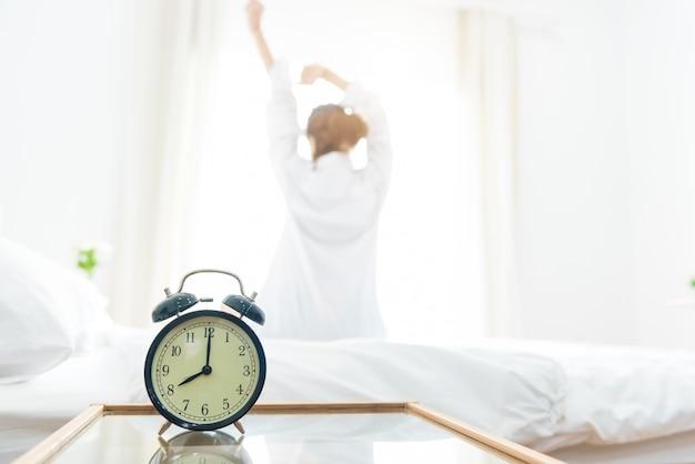 Hintere ansicht der frau ausdehnend in morgen, nachdem sie auf bett nahe fenster mit wecker aufgewacht ist