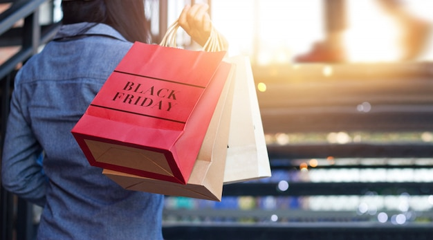 Hintere ansicht der frau black friday-einkaufstasche während treppe draußen auf dem mall halten