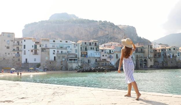 Hintere ansicht der frau, die ansicht der alten stadt cefalu auf der insel sizilien, italien genießt