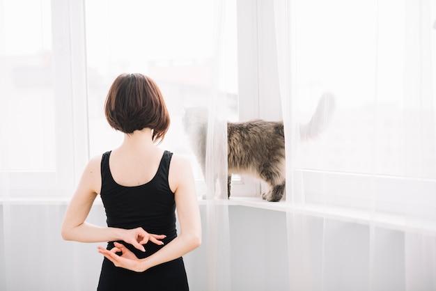 Hintere ansicht der frau die katze betrachtend, die gyan mudra geste in ihr zurück macht