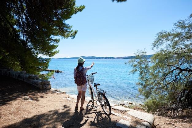 Hintere ansicht der frau, die mit fahrrad auf steinigem bürgersteig unter klarem blauem himmel steht, der auf gegenüberliegendes ufer auf funkelndem klarem meerhintergrund am sommertag zeigt.