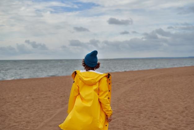 Hintere ansicht der frau im leuchtend gelben umhang und im roten hut am ufer der nordsee am kalten herbsttag
