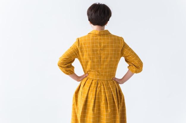 Hintere ansicht der frau in einem gelben kleid, das auf weißem hintergrund aufwirft