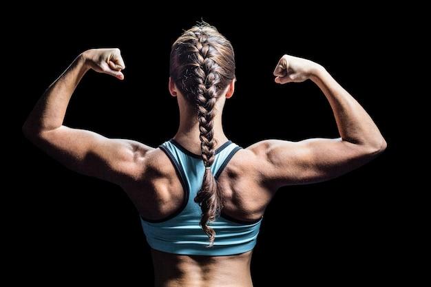 Hintere ansicht der frau mit dem umsponnenen haar, das muskeln biegt
