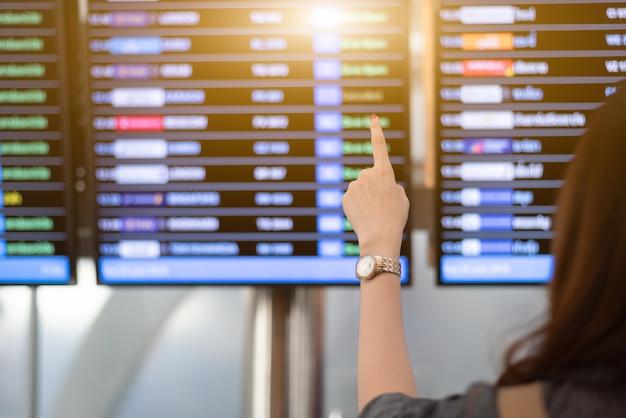 Hintere ansicht der frau nach flügen vom flugzeitplan im flughafen suchend