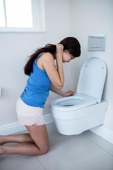 Hintere ansicht der frau oben in toilette kotzend