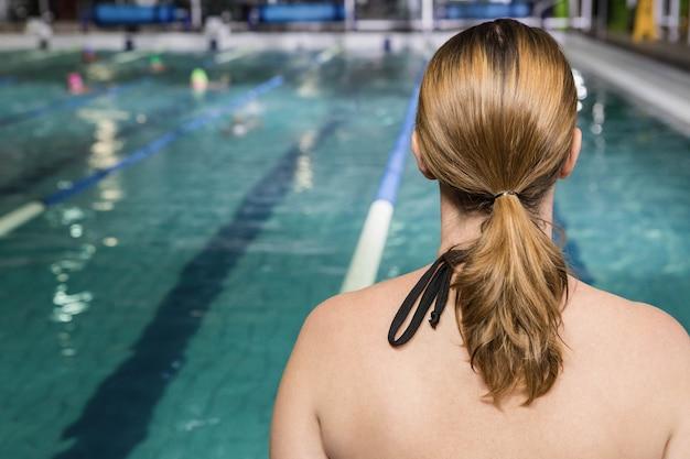 Hintere ansicht der frau sitzend am rand des pools im freizeitzentrum