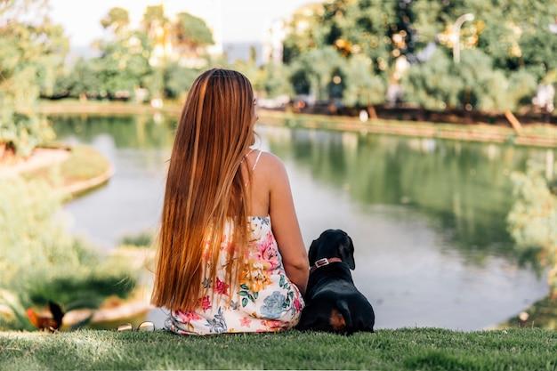 Hintere ansicht der frau und des dachshunds, die nahe dem teich sitzen