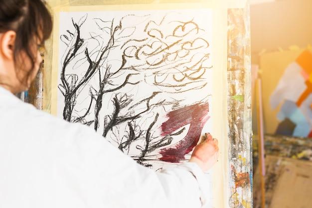 Hintere ansicht der frauenmalerei auf segeltuch an der werkstatt