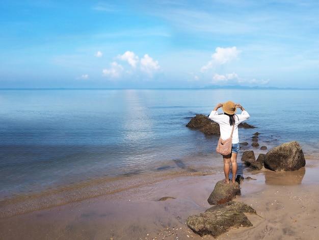Hintere ansicht der glücklichen jungen frau, die auf dem felsen steht und zum ozean schaut.