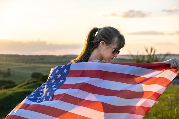 Hintere ansicht der glücklichen jungen frau, die mit usa-nationalflagge im freien bei sonnenuntergang aufwirft. positives mädchen, das unabhängigkeitstag der vereinigten staaten feiert. konzept des internationalen tages der demokratie.