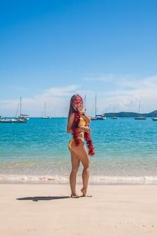Hintere ansicht der glücklichen jungen frau im bikini, der die lustigen gläser und lametta der frohen weihnachten stehen auf dem strand trägt