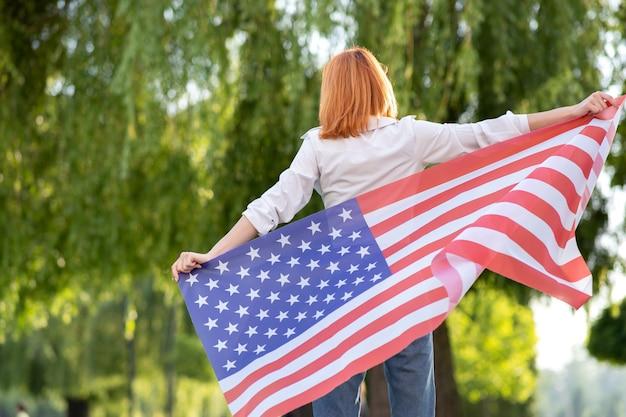 Hintere ansicht der glücklichen jungen rothaarigen frau, die mit usa-nationalflagge steht, die draußen im sommerpark steht. positives mädchen, das unabhängigkeitstag der vereinigten staaten feiert.