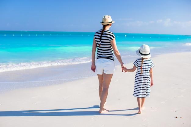 Hintere ansicht der glücklichen mutter und der kleinen tochter am karibischen strand