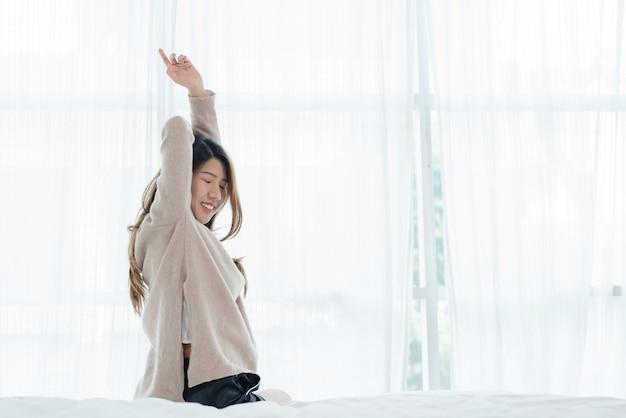 Hintere ansicht der glücklichen schönen jungen asiatischen frau, die am morgen aufwacht und auf bett sitzen