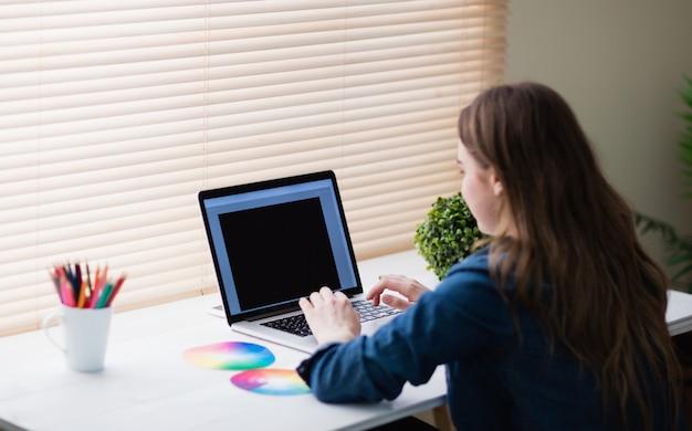 Hintere ansicht der hippie-geschäftsfrau, die laptop an ihrem schreibtisch verwendet