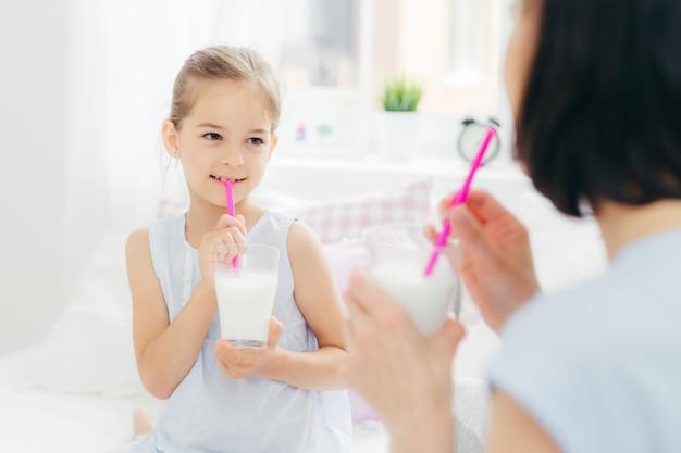 Hintere ansicht der jungen brunettemutter betrachtet ihre kleine tochter, trinkt frische milchcocktails im bett