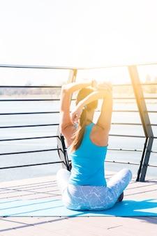 Hintere Ansicht der jungen Eignungsfrau, die ihre Hand sitzt auf Brücke im Morgensonnenlicht ausdehnt