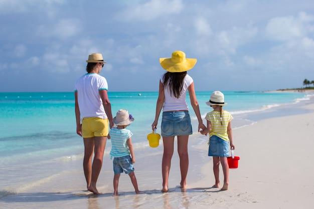 Hintere ansicht der jungen familie mit zwei kindern auf karibischen ferien