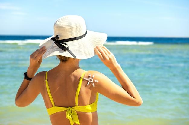 Hintere ansicht der jungen frau, die am strand mit sonnenschutzcreme in der sonnenform auf ihrer schulter bräunt. uv-sonnenbrandschutz und sonnenschutz-hautpflegekonzept