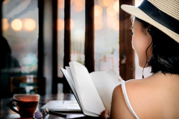 Hintere ansicht der jungen frau ein buch beim sitzen lesend in der kaffeestube.
