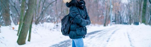 Hintere ansicht der jungen frau gehend in das unglaubliche winterorest mit enormem rucksack
