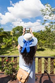 Hintere ansicht der jungen frau im hut, der foto des tropischen waldes macht
