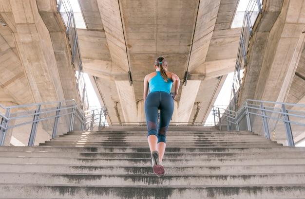 Hintere ansicht der jungen frau in der sportkleidung, die auf treppenhaus rüttelt