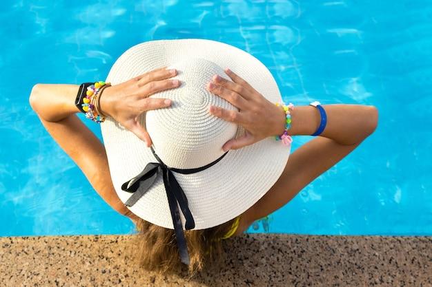Hintere ansicht der jungen frau mit dem langen haar, das gelben strohhut trägt, der im warmen sommerschwimmbad entspannt
