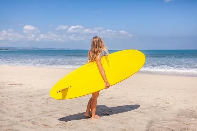 Hintere ansicht der jungen frau mit dem langen haar, welches das surfbrett sich vorbereitet zu surfen hält