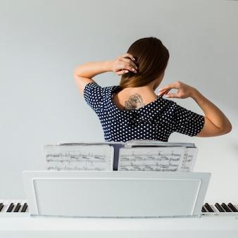 Hintere ansicht der jungen frau stehend hinter dem klavier, das zurück tätowierung über ihr zeigt