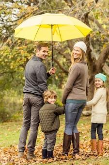 Hintere ansicht der jungen lächelnden familie unter regenschirm