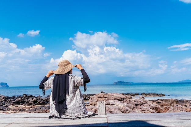 Hintere ansicht der jungen moslemischen asiatischen frau, die vom hölzernen gehweg schaut. zukunfts- und forschungskonzept. frau, die an über meer steht. reise-konzept.