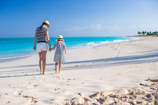 Hintere ansicht der jungen mutter und der kleinen tochter am karibischen strand
