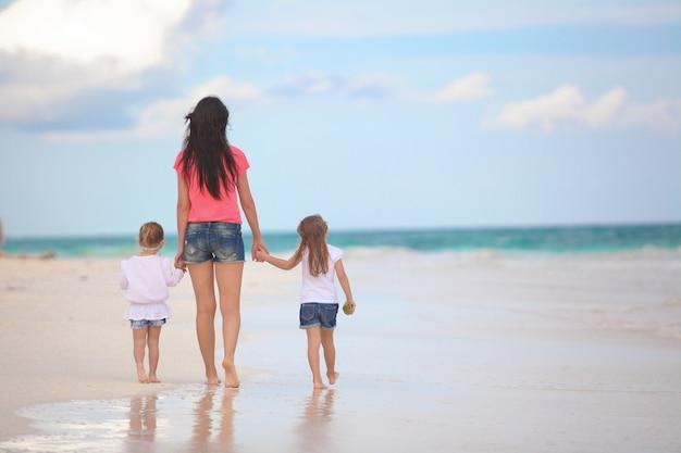 Hintere ansicht der jungen mutter und ihrer netten töchter, die am tropischen strand gehen