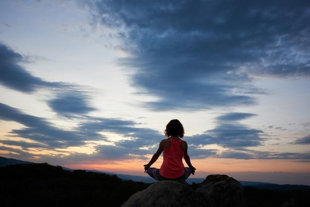 Hintere ansicht der jungen schlanken frau, die auf großem felsen in der yoga-lotushaltung auf dramatischem abendhimmel der grünen baumkronen am sonnenunterganghintergrund sitzt. konzept für tourismus, meditation und gesunden lebensstil