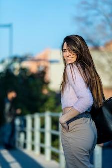 Hintere ansicht der lächelnden schönen hand der jungen frau auf der tasche, die in der straße beim an einem sonnigen tag weg schauen steht