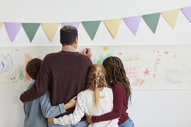 Hintere ansicht der lehrerin, die auf wänden mit multiethnischer gruppe von kindern zeichnet, während kunstunterricht an weihnachten genießen, raum kopieren