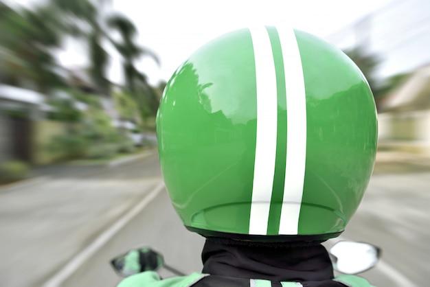 Hintere ansicht der motorradtaxifahrt mit schnellem