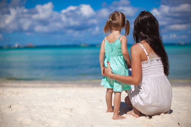 Hintere ansicht der mutter und seiner kleinen tochter, die auf dem meer tropischem strand betrachten