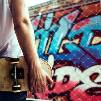 Hintere ansicht der nahaufnahme des armes skateboard mit graffitiwandhintergrund halten