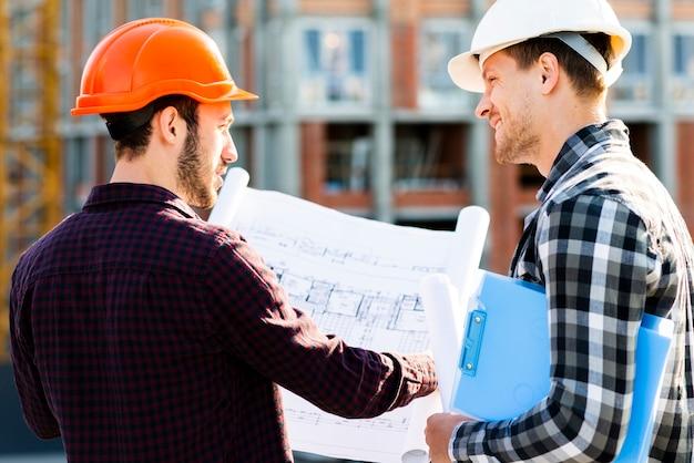 Hintere ansicht der nahaufnahme des ingenieurs und des architekten, die bau überwachen