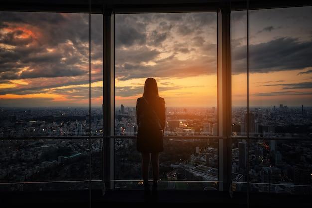 Hintere ansicht der reisendenfrau tokyo-skyline auf der aussichtsplattform bei sonnenuntergang schauend