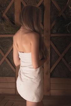 Hintere ansicht der rückenlosen sexy jungen frau, die in der sauna steht