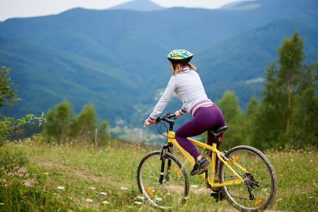 Hintere ansicht der schlanken sportlichen frau, die auf gelbem fahrrad auf einem gras in den bergen reitet. berge, wälder auf dem unscharfen hintergrund