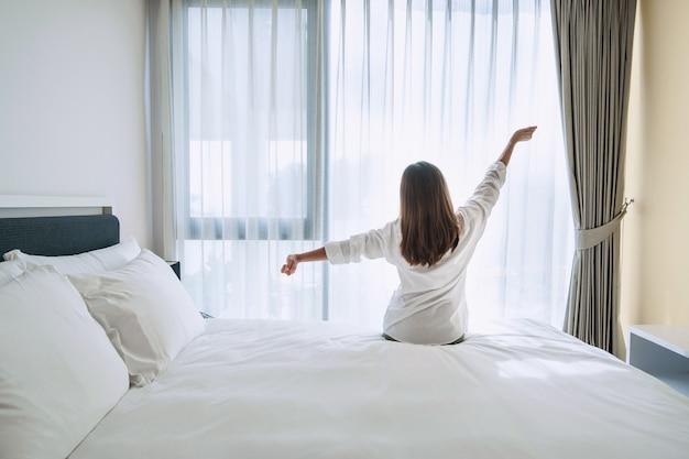 Hintere ansicht der schönen jungen asiatischen frau im weißen schlafanzug, der nach dem aufwachen am morgen auf weißem bett streckt