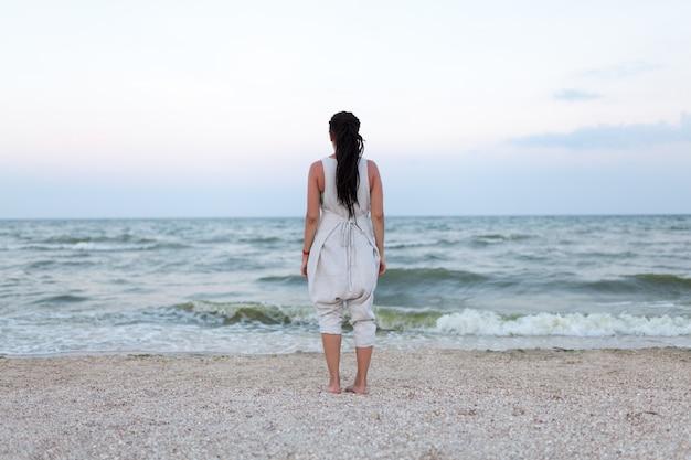 Hintere ansicht der schönheit im weißen kleid mit dreadlock